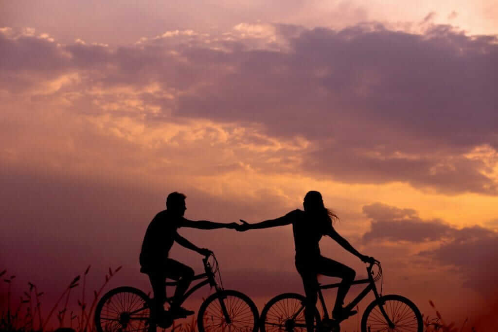 Couple Holding Hands While Bicycling
